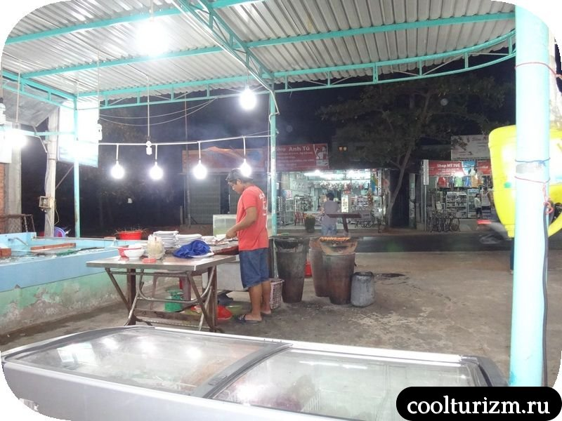 вьетнамец жарит рыбу на гриле